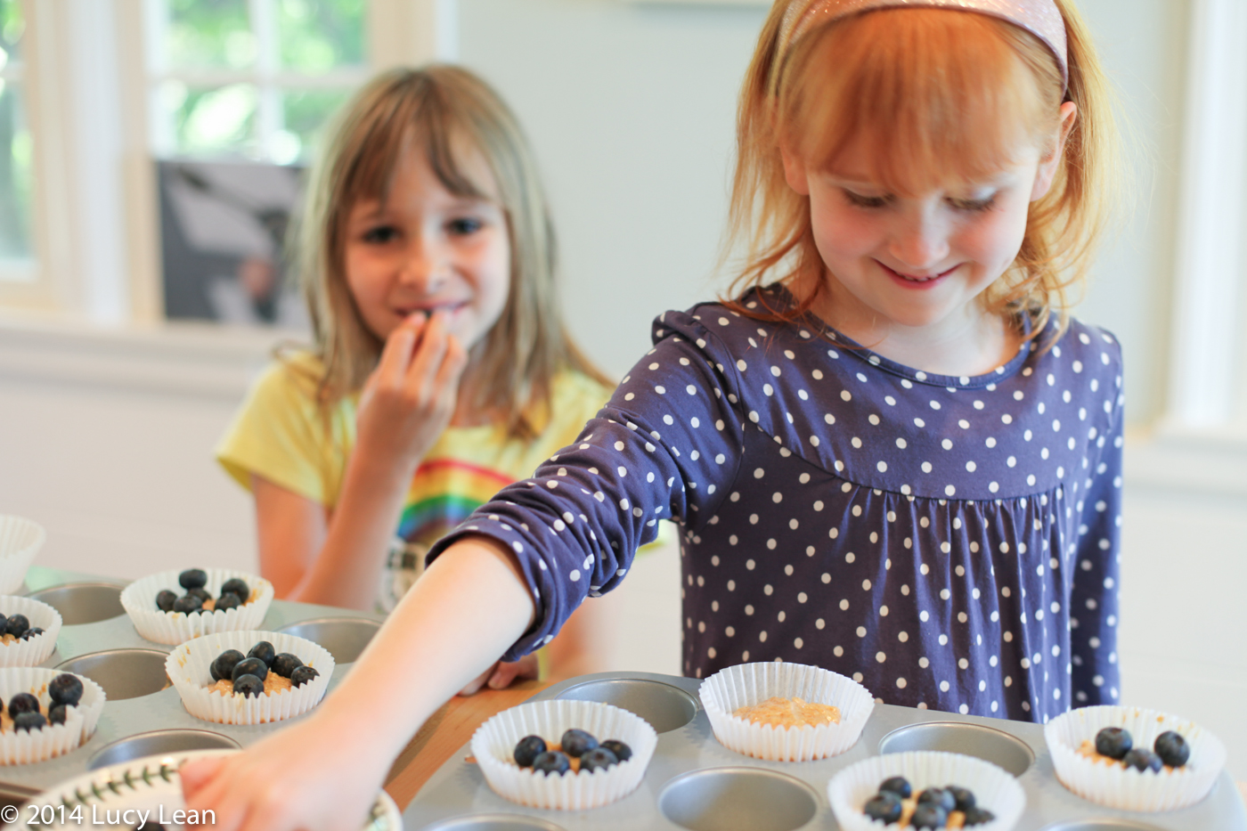 Elsie tops muffin batter with blueberries